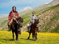 foreigner and tibetan nomad ride horses