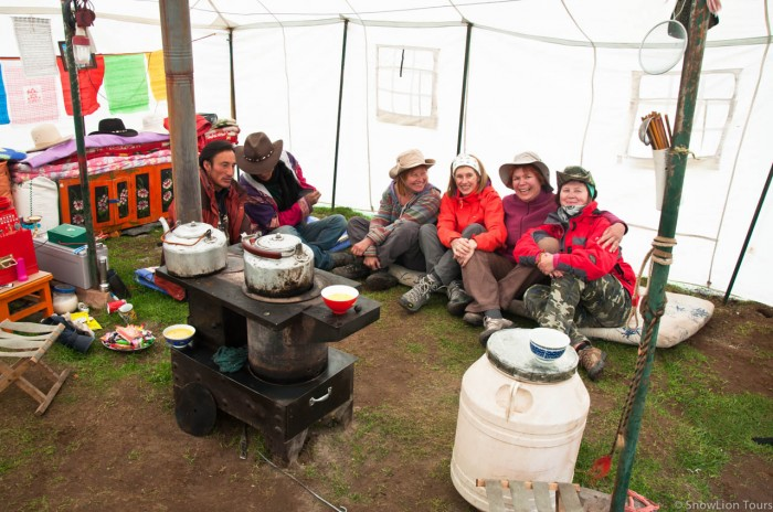 our clients enjoying make jokes with tibetan nomads in a tent in Amdo